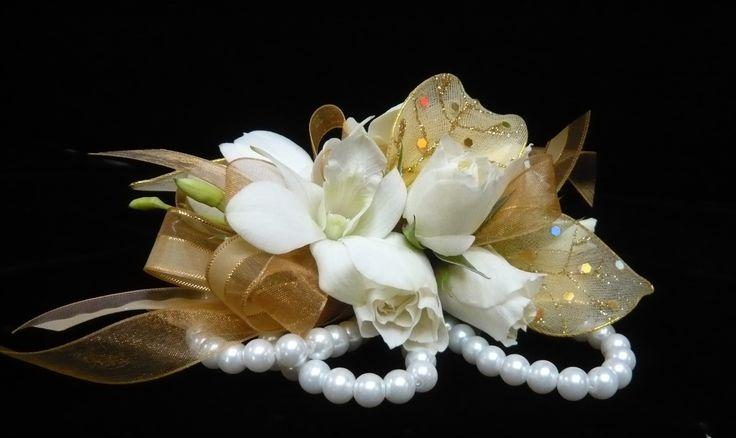 Ivory spray roses and white dendrobium orchids on gold ribbon with gold accent leaves on a pearl bracelet  wrist #corsage for #prom by Emil J Nagengast Florist in Albany, NY.