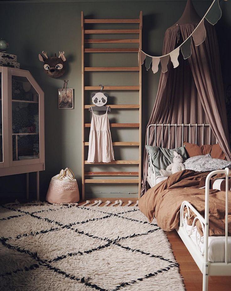 Chambre d'enfant aux tons vert, rose sale et rouille dans la confortable chambre scandinave