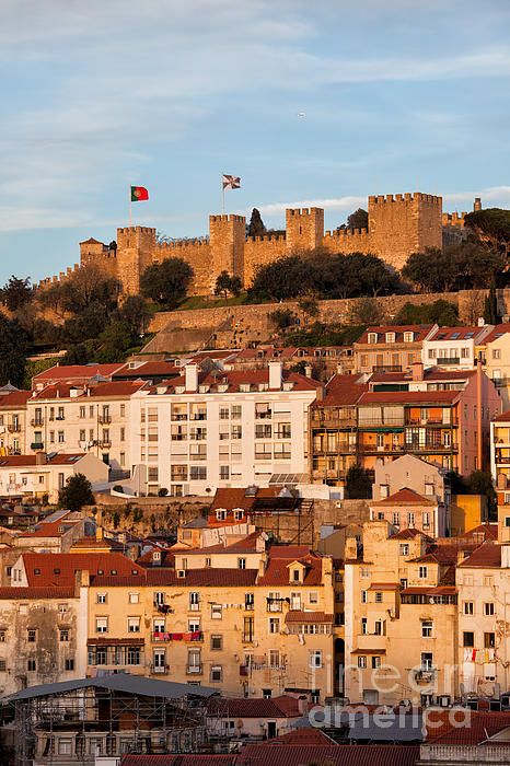City of Lisbon at sunset with Castle of Sao Jorge on top of a hill in Portugal. #lisbon #lisboa #portugal #city #sunset #castle #saojorgecastle #cityscape #houses