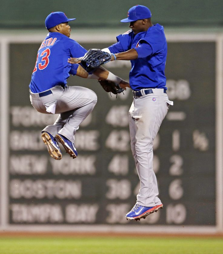 Chicago Cubs shortstop Starlin Castro leaps in celebration with teammate Junior Lake after a win against the Boston Red Sox.