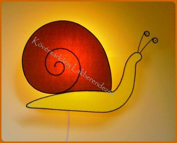"""Plüss Csiga A csiga a védekezés, a biztonságra törekvés, és a türelem jelképe. A """"csigavonal"""" ez a természetben rendkívül elterjedt forma, az élet folyamatos fejlődését jelenti. A csiga segít az okos előrelátásban és a megfontolt haladásban. Méretei: Szélesség: 56 cm Magasság: 38 cm. Ára ufólámpatesttel: 10.000 Ft"""