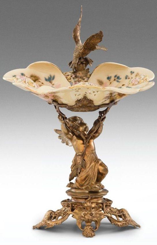 Zsolnay neorokokó asztalközép Öntött, patinázott és aranyozott bronz talapzaton porcelánfajansz tálka. Porcelánfajansz tálkáján hullámos és áttört peremszél,ill. egész felületén magas tüzű, színesen festett és aranyozott virágdekor. Tál alján jelzett: masszába nyomott Zsolnay Pécs és 3568 (1891. évi formaszám), valamint pirossal bélyegzett Made in Hungary. Zsolnay Pécs, 1891. M.: 42 cm 17/750