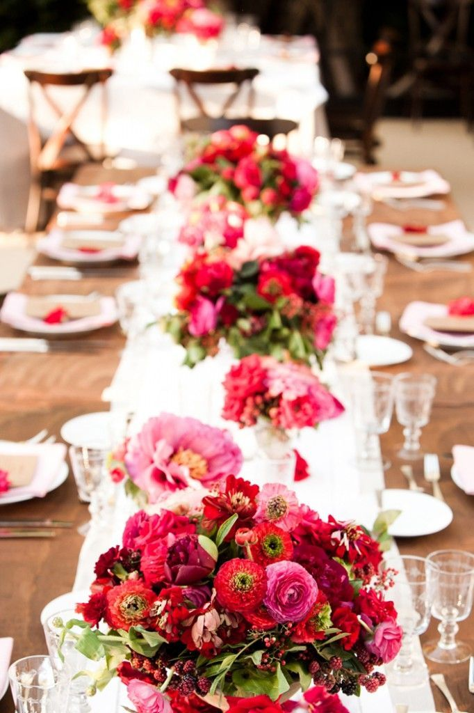red, raspberry & pink centerpieces on long table with ...
