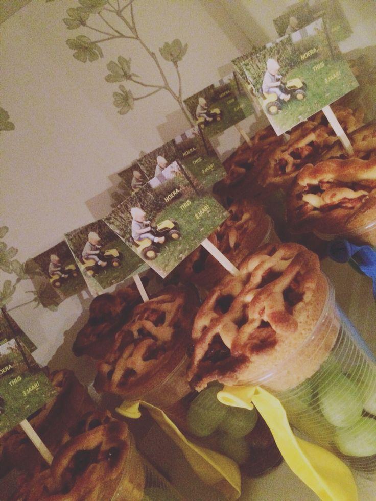 Traktatie! Miniappeltaartjes in een plastic bekertje met druifjes en rozijnen. Ballonnetje erbij en een prikker met foto.. Klaar!