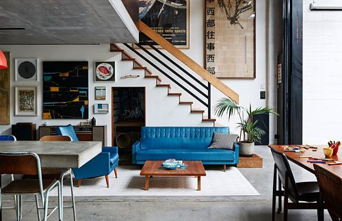 Blue couch, cheerfully cluttered walls.