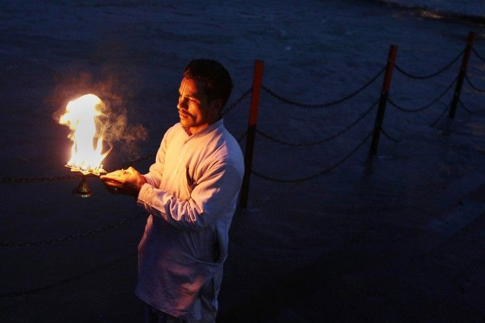 """Haridwar, India. In India """"Puja"""" are ceremonies of adoration for hindu people. Arati Puja is the fire ceremony celebrated usually near the sacred banks of Gange river. During the Kumbh Mela festival, every twelve years, holy men officiate this function in the dark before sunrise and before sunset."""