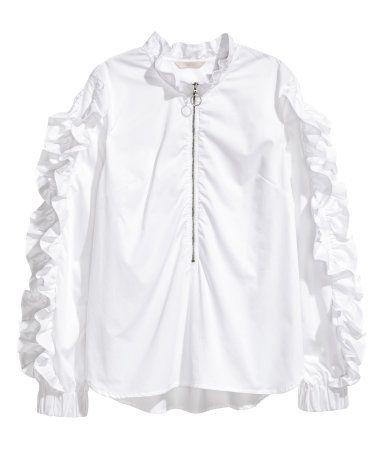 Wit. Een blouse van satijn met een volantrandje langs de halsopening en lange mouwen met volants overlangs en breed elastiek onderaan. De blouse heeft een