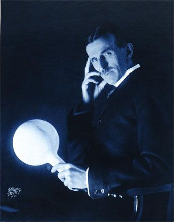 Nikola Tesla holding a lightbulb that is being lit with wireless electricity. - Imgur