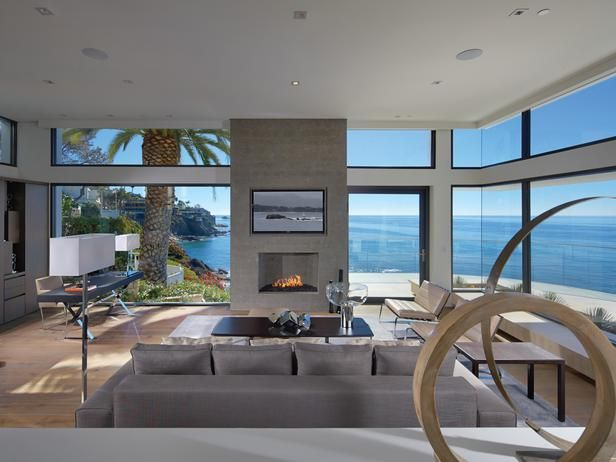 The line between the indoors and outdoors blurs when floor-to-ceiling windows surround the living room. A neutral color palette puts the emphasis on the beautiful, colorful view while the modern furnishings and rectangular motif emphasize the landscape and horizon line.