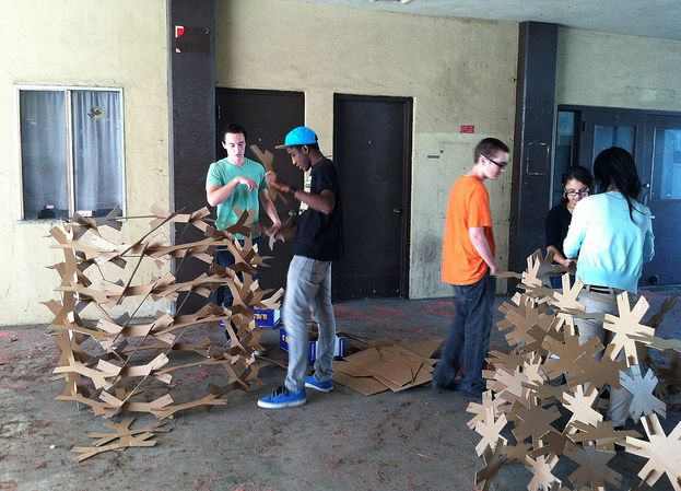 """A few weeks ago, our fifth period class started a project called """"Unit(ed) We Stand,"""" in which students designed a small-scale cardboard building unit in two dimensions, which could be put together to create a 3-d enclosure. Students learned how to use the laser cutter and Adobe Illustrator to draft and cut hundreds of the units, then prototyped a structure made from them. Then we took it to full scale, cutting hundreds more of the units at a larger size, by hand (no laser cutter this time)."""