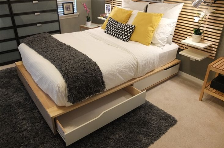 IKEA Share Space.  Analyze- White sheets, coverlet, standard pillows and Euro, dark grey at foot of bed, dark grey rug, pop of yellow in decorative pillows and black, geometric lumbar.  Notice Euro and standard pillow same color - white