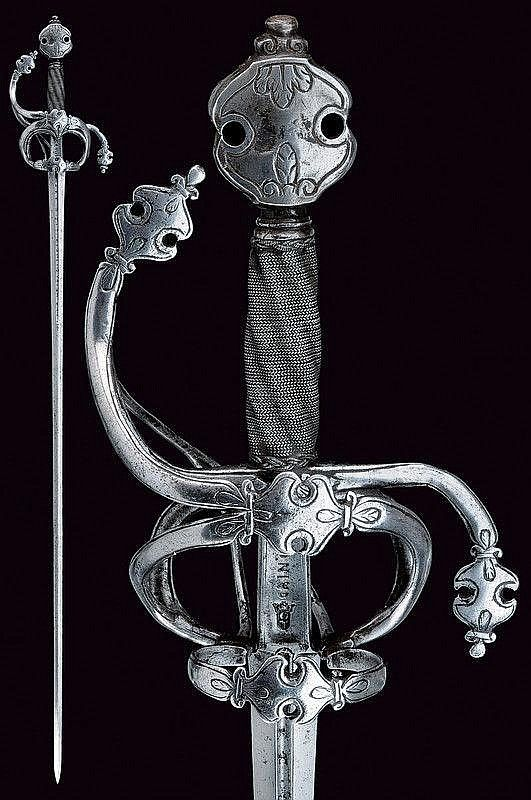 "Description: A rapier with Caino mark. Late 16th Century: North Italy. Straight blade of hexagonal section, with central grooved at the forte, featuring unclear inscriptions, concave ricasso with stamp and mark ""CAINO"" on both sides; iron hilt with arms of the hilt, with ring and lower-ring chiselled and engraved with floral motifs. Pommel decorated en suite. Grip with iron wire binding and moor's heads. Length 125 cm."