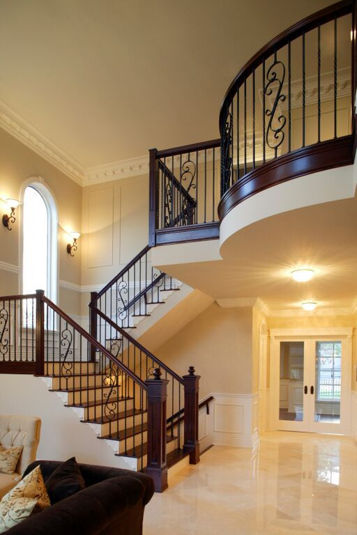 A beautiful staircase with a stylized wrought iron railing, sconce lighting, and richly stained natural wood elements. What do you think of the railing design?
