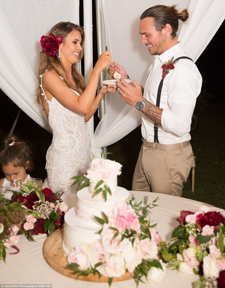 Classy:The bride and her spouse took turns feeding the white cake to each other, avoiding smashing it in each other's faces as some couples do