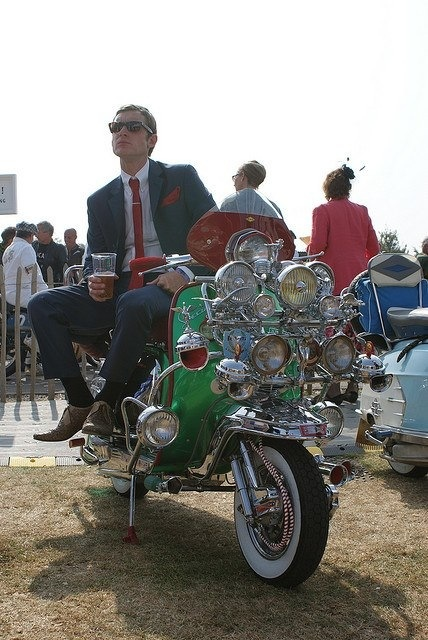 A Mod on his scooter having a pint. Lookin' dapper as usual.