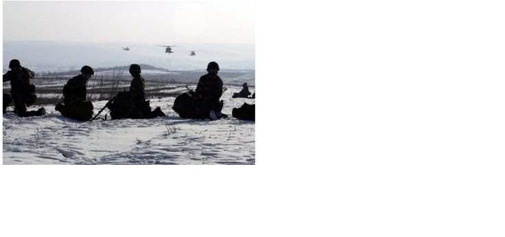 Soldiers wait on the snow covered ground as UH-60 Blackhawks approach the Heritage Drop Zone near Klina, Kosovo, after an airborne assault, in support of Operation JOINT GUARDIAN II