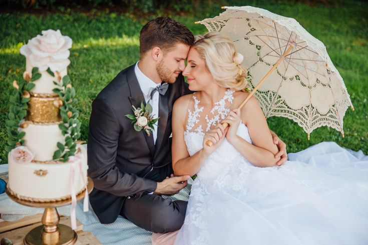 charming czech inspirational shoot with romantic wedding picknick with a four tiered pinka and gold wedding cake and a lace parasol.