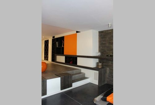 Het lager gelegen vloergedeelte is een gepolierde betonvloer kleur antraciet.  Het hoger gelegen gedeelte werd afgewerkt met een keramische parket.