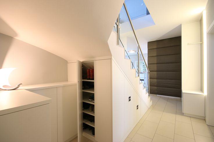Die Tischlerei Boldt Innenausbau GmbH in Leipzig entwarf und fertigte diese Einbaumöbel unter einer Betontreppe im Rahmen einer konzeptionellen Neugestaltung des Eingangsbereiches. Die gepolsterte Wandverkleidung dient dabei der Verbesserung der Raumakustik. Der Untere Teil ist demontierbar und verdeckt die HKV der Fußbodenheizung. Die Einbauten befinden sich im Durchgang von der Garage zur Eingangshalle.  Treppenunterschrank, Treppenschrank, Schuhschrank,