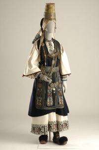 This bridal costume of the Pindus-mountain Nomads was worn by the Arvanitovlachs (Albanian-Vlachs) called the Karagounides of Epirus. It consists of a white chemise with embroidery at the hem and bib, a black segouni (sleeveless coat) and a woven apron. Additional human hair braids are fastened to the hair, and the headdress consists of a tall cone-shaped hat with a silver band around its base as a diadem. Silver chains on the chest, a buckled belt (the kemeri) and bracelets complete the…