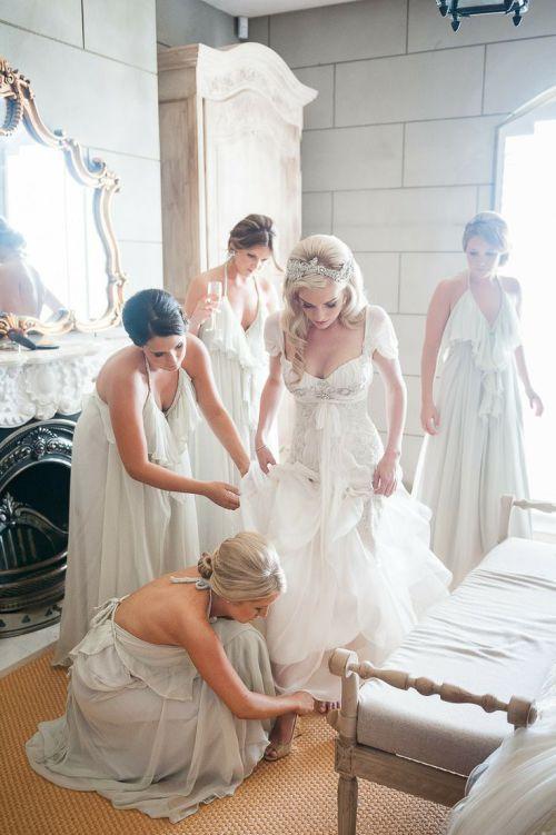 Damas de honor ayudando a la novia a vestirse