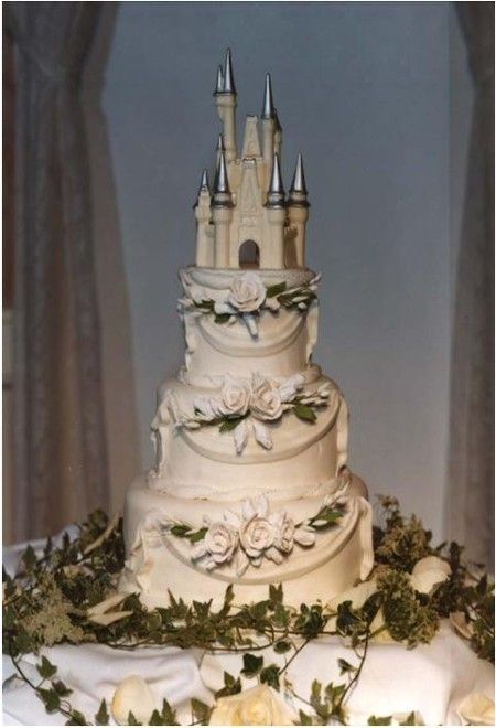 A true fairytale cake in white and silver with a Cinderella's castle cake topper.
