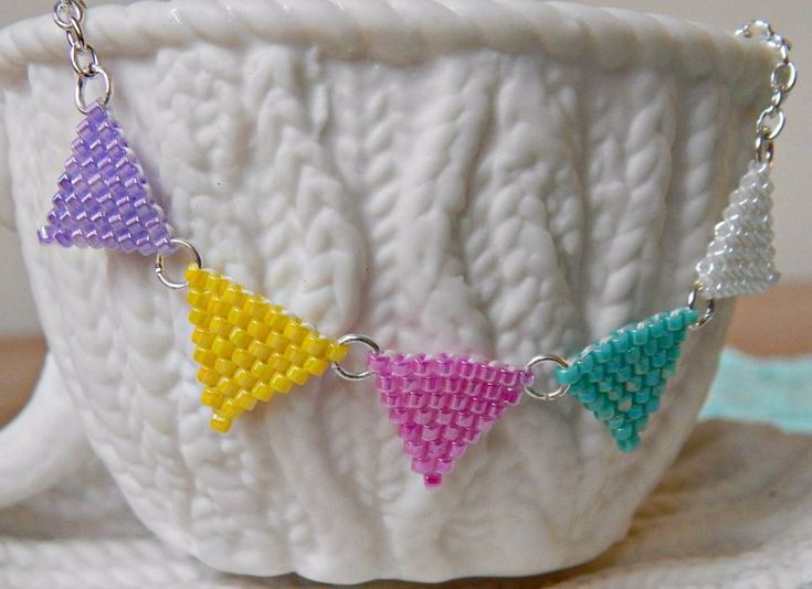 Prepare to stitch up a storm with this too-cute brick stitch tutorial! Make an adorable Brick Stitch Bunting Necklace when you follow this awesome jewelry making video tutorial.