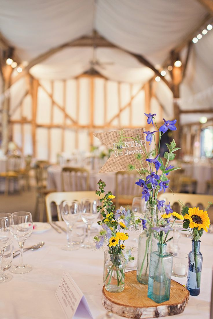 Rustic Tree Slabs & Flower Stem Filled Bottle Centrepiece | Blue & Yellow Themed Wedding at South Farm in Cambridgeshire | Sunflower bouquet | Photography by Bea | http://www.rockmywedding.co.uk/katie-mike/