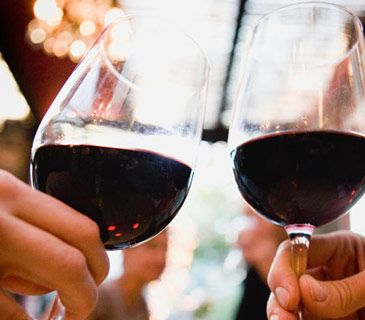 <p>Hands holding glasses of red wine in restaurant</p>