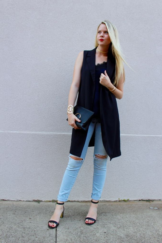 dinner downtown outfit, night out. Silk camisole with long, open front vest. Distressed, ripped jeans. Block heels. Black clutch. On trend