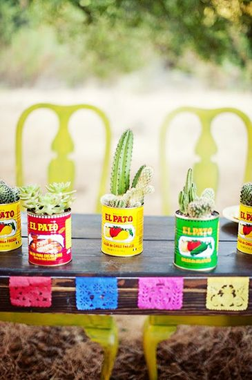 Set out small potted cacti in lieu of flowers, and make the arranging a little easier on yourself. Instead of a basic terracotta pot, place yours in a bright can of salsa or enchilada sauce for a nod to the cuisine that's not only bright and cheerful, but alsoaffordable! Let guests each take one home as a memorable keepsake.