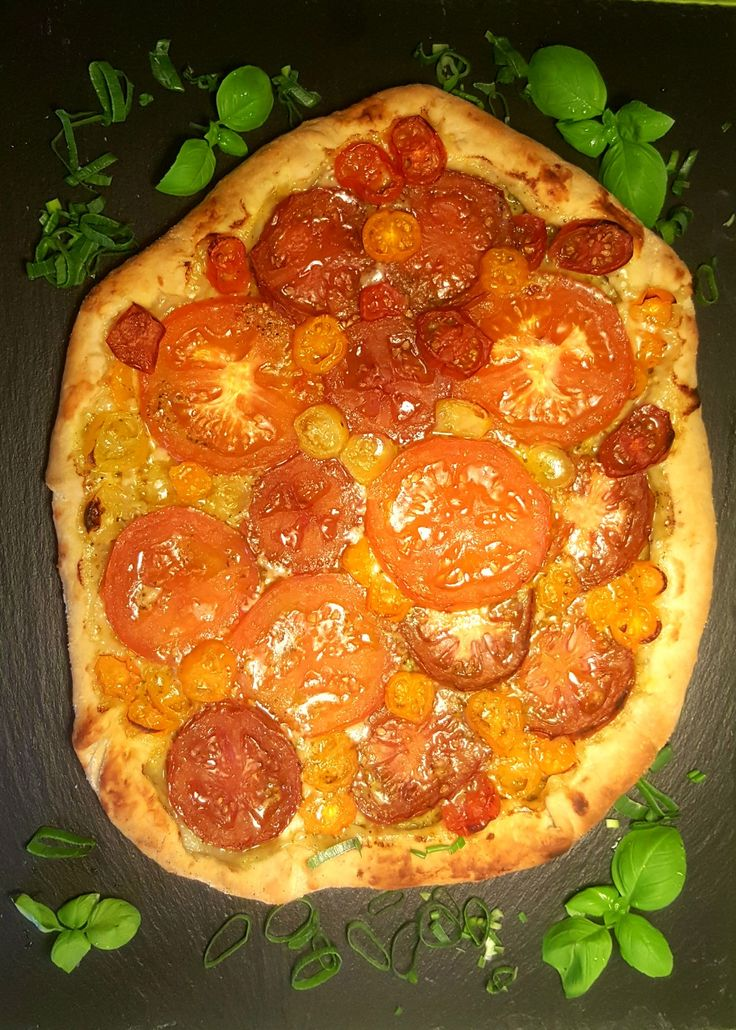 Amazing tomatoe pizza with parmesan and green mango coriander souce and colourful tomatoes layers