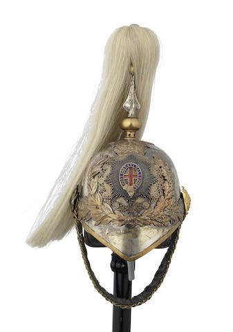 An 1871 Pattern Full Dress Helmet Of An Officer In The 1st Life Guards - Early 20th Century -  The white-metal skull complete with all its embossed copper fittings, ornate frontal plate displaying a crowned shield bearing a double enamelled Garter on a silver diamond-cut star, all above attendant sprays of laurel and oak, St. George slaying the Dragon between, large rose-pattern supporters with leather-lined chin-chain, the interior with buff-leather liner and green leather peak lining...