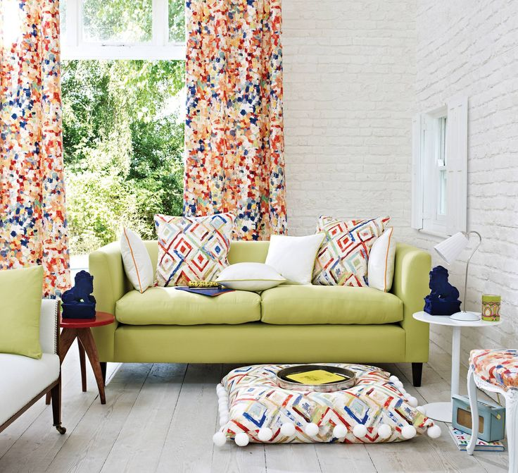10 ways to accessorise your living room with textiles - a colourful eclectic living room with multicoloured patterned curtains and green sofa
