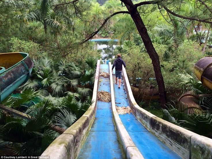 A visitor walks over dried palm leaves down one of the slides in the abandoned water park