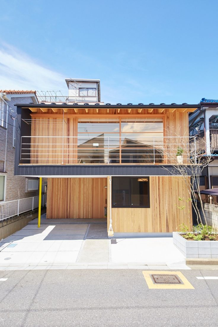 Facade of modern Japanese home outside Tokyo. Designed for ventilation during peak summer temperatures, this three-story modern home outside of Tokyo uses traditional Japanese interior design strategies. The climate was one of the biggest design challenges for co-designstudio's Yanagisaki House, especially when the clients desired a low-energy, mostly passively cooled home.