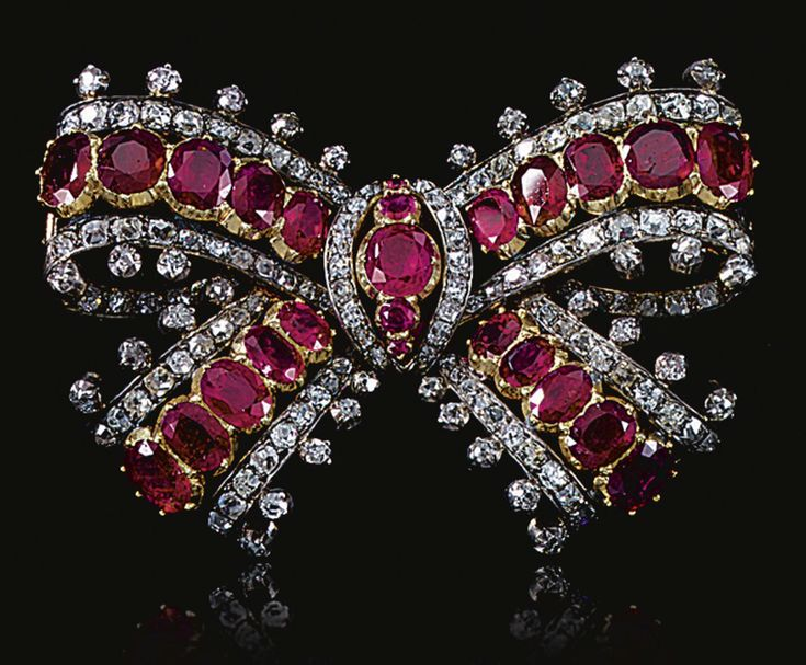 RUBY AND DIAMOND BOW BROOCH, MID 19TH CENTURY.  Designed as a ribbon tied bow set with graduated lines of oval rubies mounted in cut-down collets bordered with lines of old-mine and circular-cut diamonds.