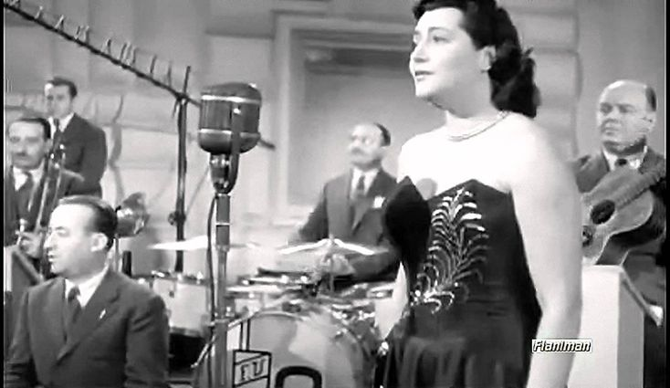 "Nilla Pizzi sings ""Vola colomba"" [Fly Dove] (1952), with conductor Cinico Angelini and his Orchestra. This song won the second Sanremo Italian Song Festival. (Sequence added to Giuseppe Bennati's musical comedy ""Il microfono è vostro"" [The microphone is yours], 1951.)"