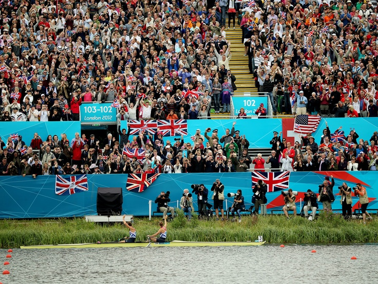 Rowers Helen Glover and Heather Stanning wave to spectators after their win in the coxless pairs brought Team GB its first gold medal of the Olympics Photographer: Graeme Robertson for the Guardian