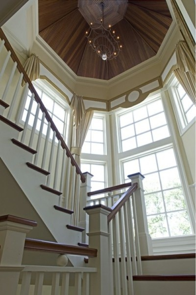 This staircase, of cherry wood and white, gains magnificence from a landing surrounded by a semi-circular wall of tall windows, and a high, high up peaked wooden tower ceiling.