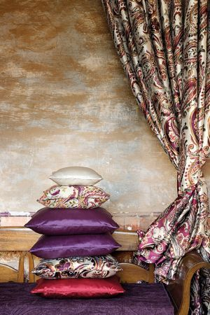 Lizzo - Paisley Fabric Collection - Stack of cushions; pink, purple, white and paisley print, with paisley print curtains, a solid wood bench, and a purple seat cushion