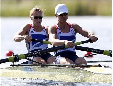 315a The image frames Heather Stanning and Heather Glover during a strenuous competition. It pictures them rowing in time with one another, they are the main focus of the image. Both atheletes are fully submerged in the sport.