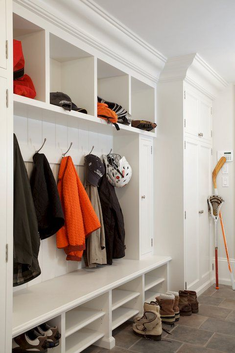 Kids mudroom design with built-in cabinets featuring open top cubbies, open lockers and shelves for shoes