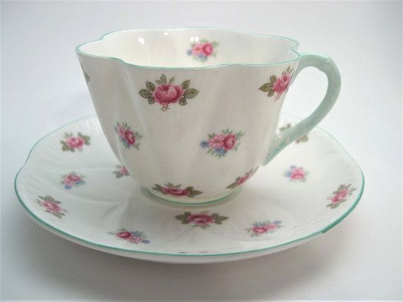 Beautiful tea cup and saucer from Shelley, England Model: Rosebud, white with pink rosebuds. The rim of the tea cup and the saucer as well as the thunbrest are mint green. Both pieces are embossed C. 1945 - 1966 Cup Measures: 2 1/4 high & Saucer Measures 5 3/4 diameter Very