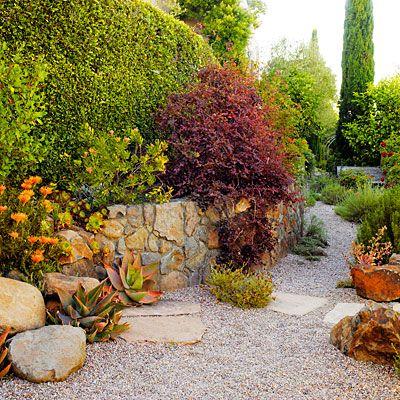 For bolder boulders, add plantings such as large, rich rosettes of coral aloe (Aloe striata) and fringe flower (Loropetalum chinense 'Razzleberri').