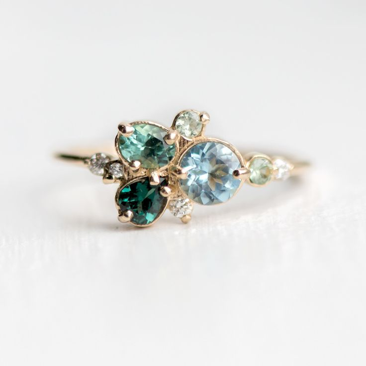 The Underwater Garden ring features a cluster of natural, genuine gemstones including aquamarine, color changing garnet, tourmaline, green sapphire and white diamonds, prong set on a solid 14k yellow