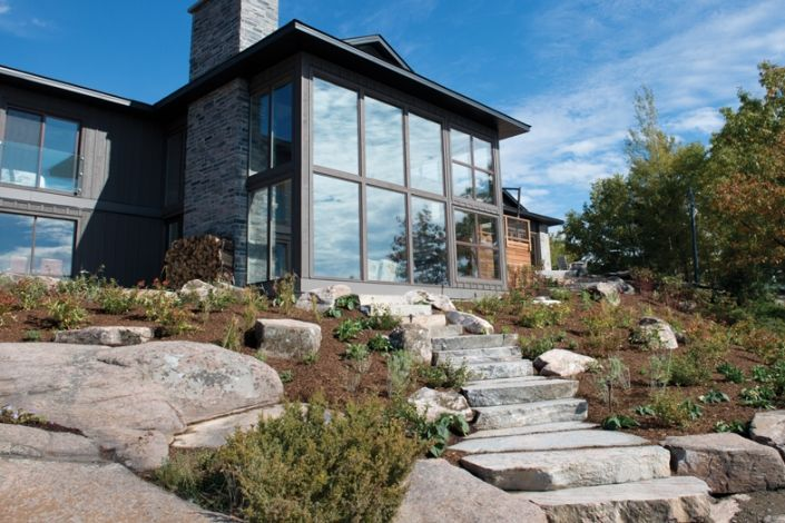 A beautifully flowing granite staircase with a calibrated seven inch tread rise lifts you effortlessly from the rocky shores of this year round Georgian Bay cottage. Though recently installed, the natural faced granite treads, mossy boulders and flamed softened stone edges give the impression that the steps have been there for years. Granite product from the Muskoka Rock Company.
