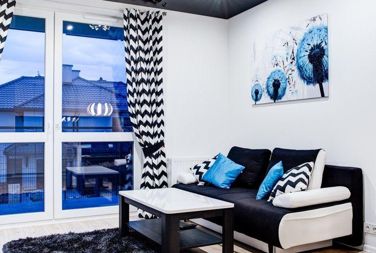 Czarno-białe wnętrze salonu z niebieskimi dodatkami. Nietypowy napinany sufit, optycznie powiększa wnętrze, tworząc lustrzane odbicie. Mała, zgrabna modułowa sofa plus poręczny stolik tworzą idealne miejsce na wieczory przed tv.