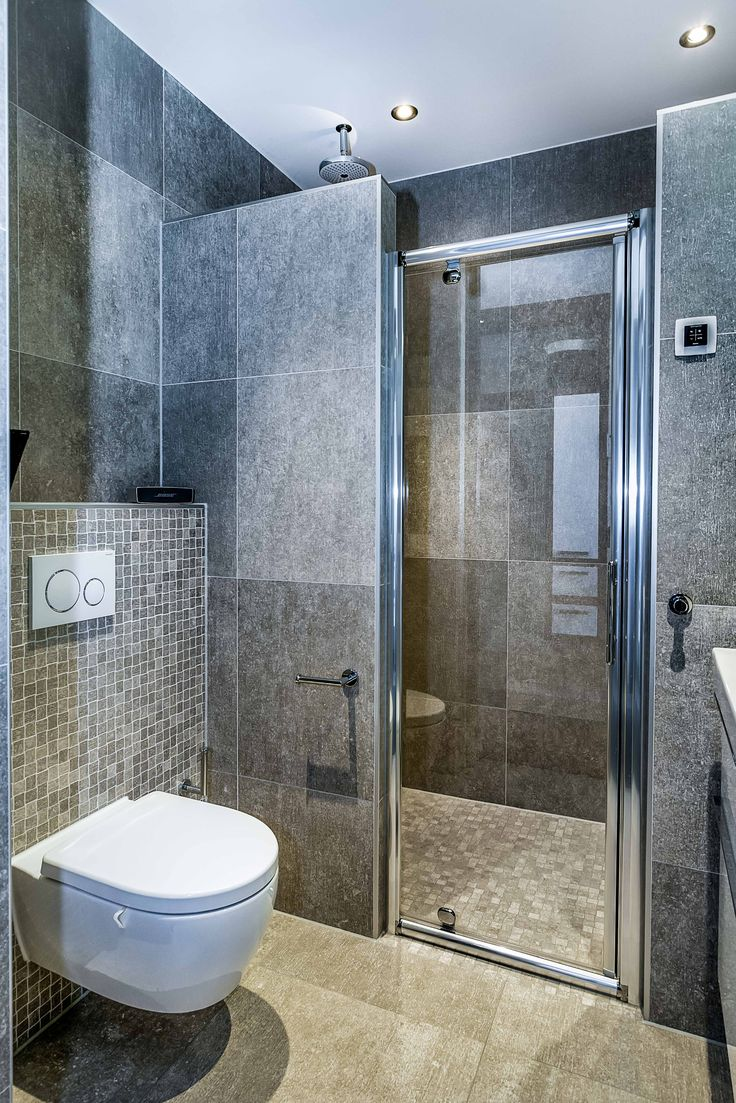 Grijze tegel in kleine badkamer, ruitme goed benut. glazen deur.