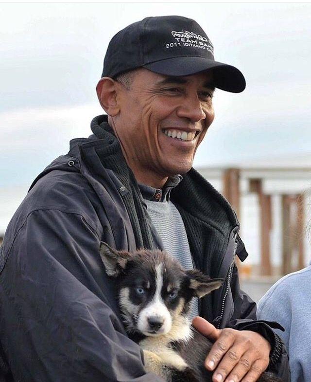 Obama holds a puppy while visiting musher John Baker and his family in Kotzebue, Alaska on September 2, 2015
